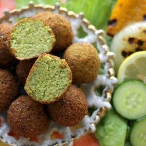 A small dish of falafel next to a plate of grilled vegetables.