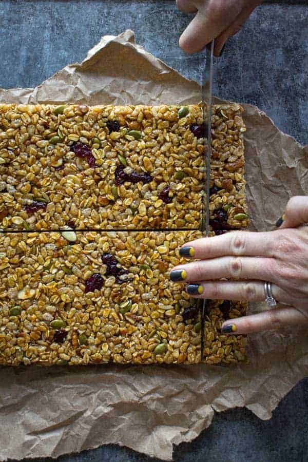 Brown butcher paper laying on top of a metal table. On top of teh paper is a rectangle made of homemade cereal bars. A woman has cut the rectangle in half, lengthwise and is using a large knife to cut the rectangle down into smaller