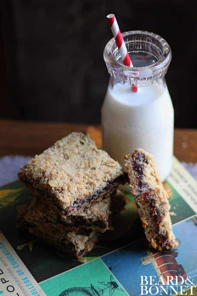 3 date bars stacked on top of one another with a 4th propped next to it. They are all sitting on top of a text book that is green and blue and there is a small bottle of milk with a red and white stripped straw in it next to the book.