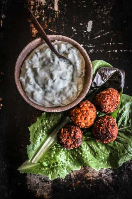 A bowl of Homemade Tzatziki Dip next to sweet potato falafel lettuce cups