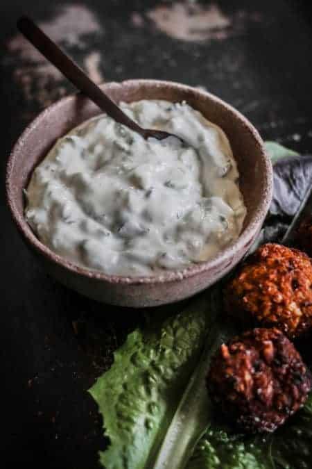 A bowl of homemade tzatziki dip next to a platter of sweet potato falafel