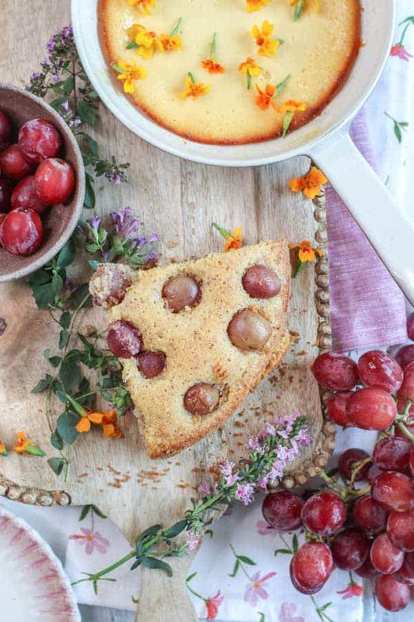A big wedge of Olive Oil Cake with Polenta and Roasted Red Grapes next to a dish of baked ricotta and a bowl of fresh grapes