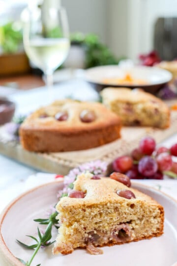 A slice of Olive Oil Cake with Polenta and Roasted Red Grapes recipe on a plate next to a glass of wine