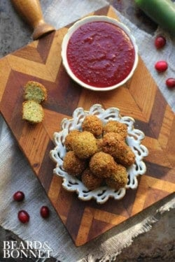Stuffing Poppers with Cranberry Jalapeno Dipping Sauce on a wooden board