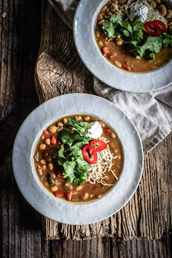 2 bowls of Chickpea and White Bean Chili on table garnished with cheese, cilantro leaves, spur cream, and sliced peppers