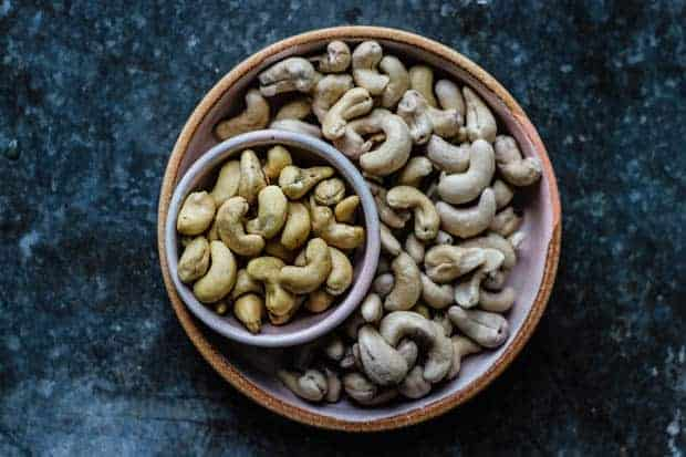 A plate of soaked raw cashews is on a metal table top. there is a smaller bowl of unsoaked raw cashews nestled into th eplate to demonstrate the difference in size