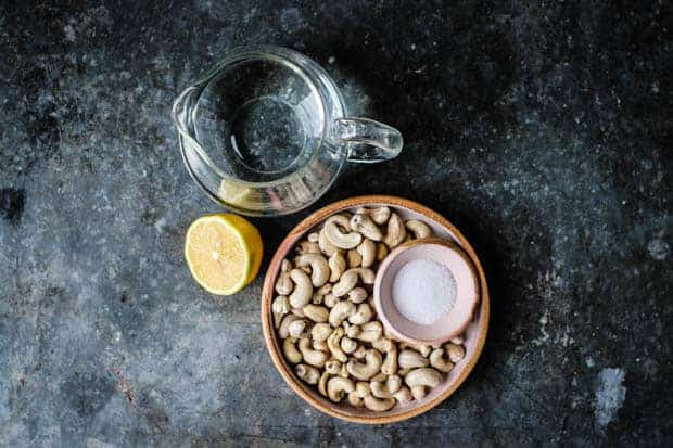 A small glass pitcher of water sits next to alemon half and a plate of cashews on a metal table