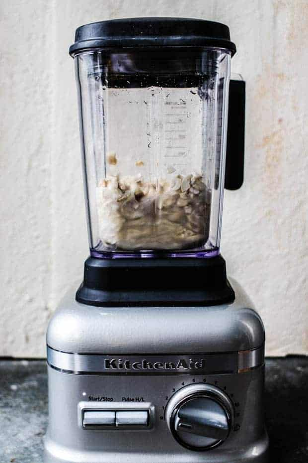 A kitchen aid blender filled with the ingredients to make cashew cream
