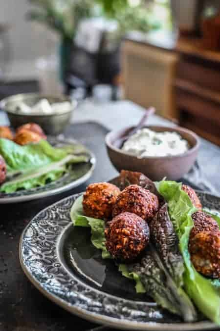 2 plates on a table with falafel and lettuce wrap ingredients on them
