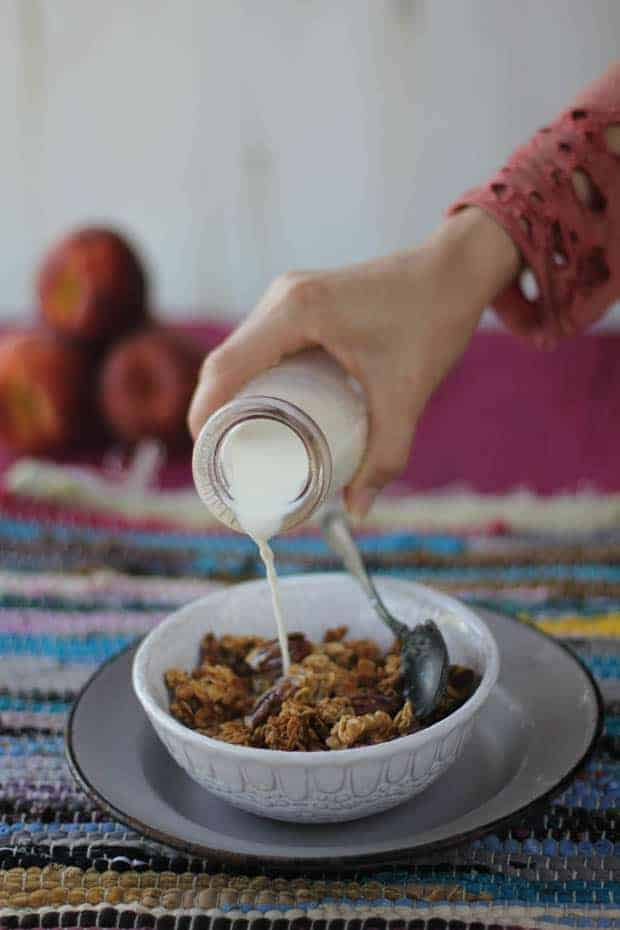 A white bowl of granola is sitting on top if a gray enamelware plate on a multi-colored woven placemat. There is a woman's hand pouring milk from a clear glass milk jug into the granola. The woman is wearing a coral colored long sleeve shirt with a decorative edge around the cuff. The table underneath the placemat is magenta and there are 3 peaches stacked up in the background.