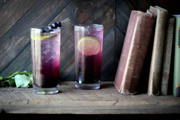 2 tall clear glass filled with ice and a purple ombre drink on a wooden book shelf next to 4 vintage books that are leaning to the right side of the image.