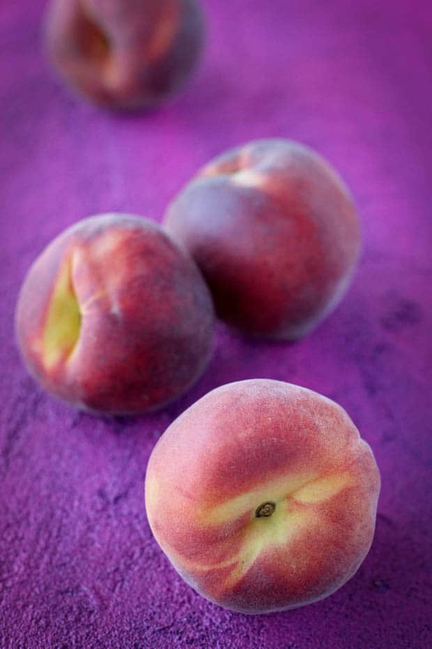 3 ripe peaches sitting on top of a magenta colored background