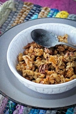 Peach cobbler granola in a white bowl is sitting on top of a gray enamelware plate. The plate is on a multicolored woven placemat that is on top of a magenta colored table.