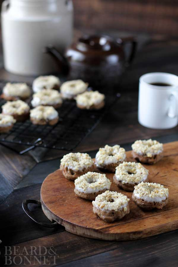 7 mini banana bread donuts on a wood cutting board with more mini donuts on a wire rack behind it. A white coffee mug filled with coffee is next to the cutting board as well as a brown tea pot