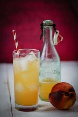 A glass of peach and ginger soda with a red and white straw sits next to a bottle of soda syrup and a fresh peach. The background of the image is magenta.
