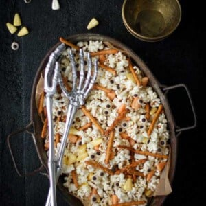 Sppoky popcorn mix with popcorn, candy corn, pretzel sticks, and candy eyeballs in an oval serving dish with skelteon hands serving spoons.