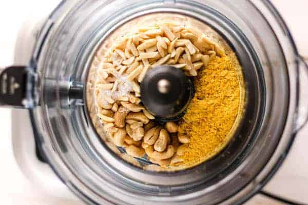 The ingredients for vegan Parmesan cheese in teh bowl of a food processor.
