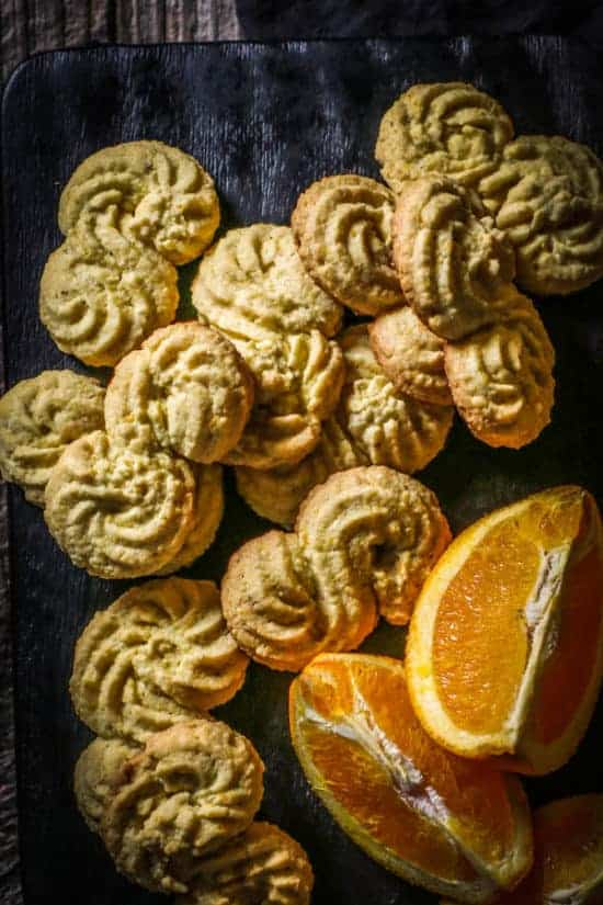 Gluten Free Italian Polenta Cookies and wedges of fresh citrus on a black wood board