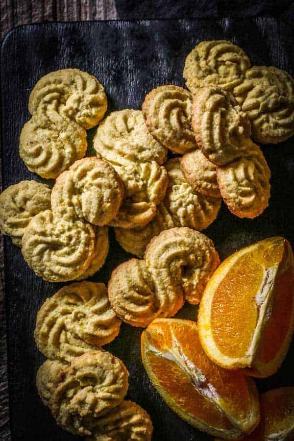 Gluten Free Italian Polenta Cookies and wedges of fresh citrus on a black wood board