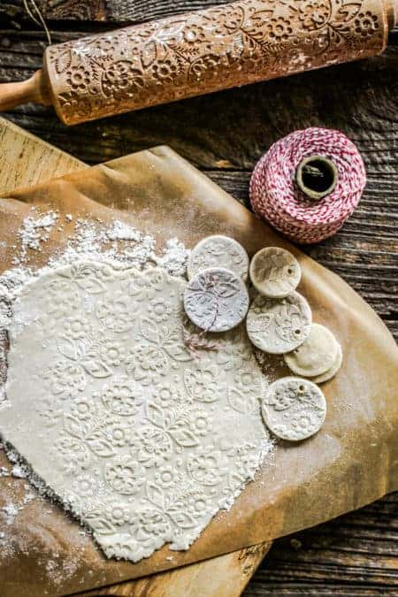 A baking scene with salt dough rolled out on parchment the imprinted with a design. Next to the dough are a few finished salt dough ornaments a spindle of red and white string and a rolling pin that has a relief pattern carved in the dough.