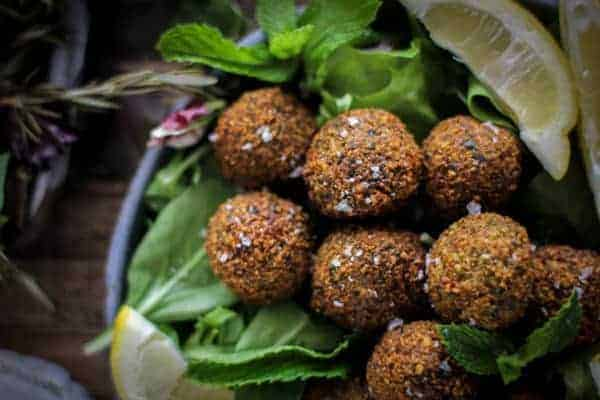 8 golden falafel on a bed of greens with lemon wedges