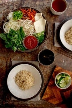 A table set up of pho noodles in bowls and all of the toppings on platters around them for building a bowl of pho