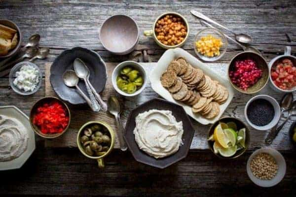 A table top spread of small bowls filled with hummus and toppings