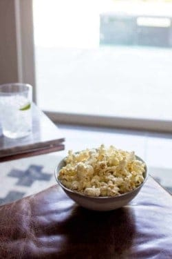 A big bowl of popcorn is sitting on an ottoman