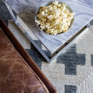 Cacio e Pepe Popcorn in a bowl on a marble coffee table next to a letter couch