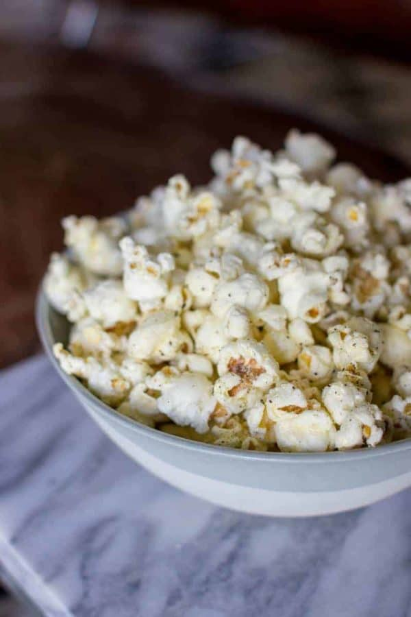 A big bowl of cacio e pepe popcorn sits on a marble table top.