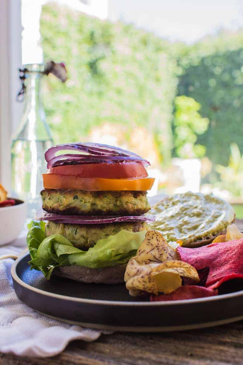 A double decker Zucchini Fritter Veggie Burger iced high with colorful toppings
