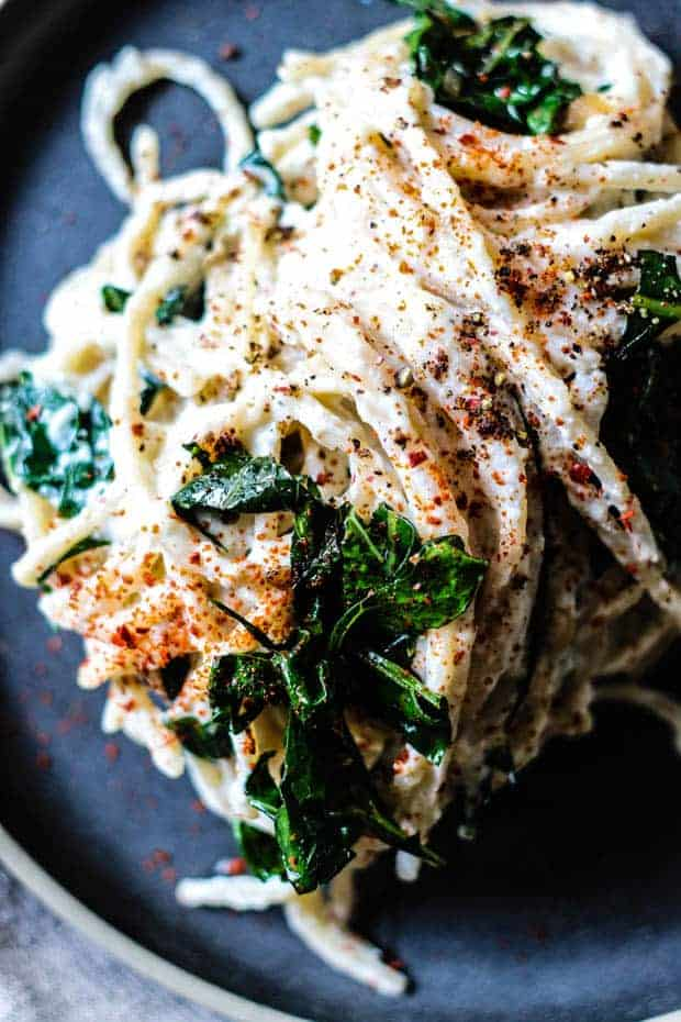 Lomg strands of pasta coated in a white cheesy sauce is piled high on a black plate. There are little pockets of cooked greens throughout the pasta dish. It has red and black pepper sprinkled on top.