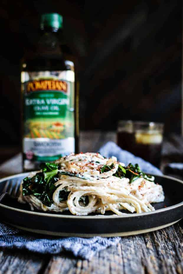 white cheesy Pasta is piled high on a black plate on top of a weathered wooden table top. There are cooked greens iced into the pasta. Underneath the plate is a blackened white houndstooth napkin. Behind the plate on the table is a bottle of Pompeian Smooth olive oil and a glass with a drink inside.