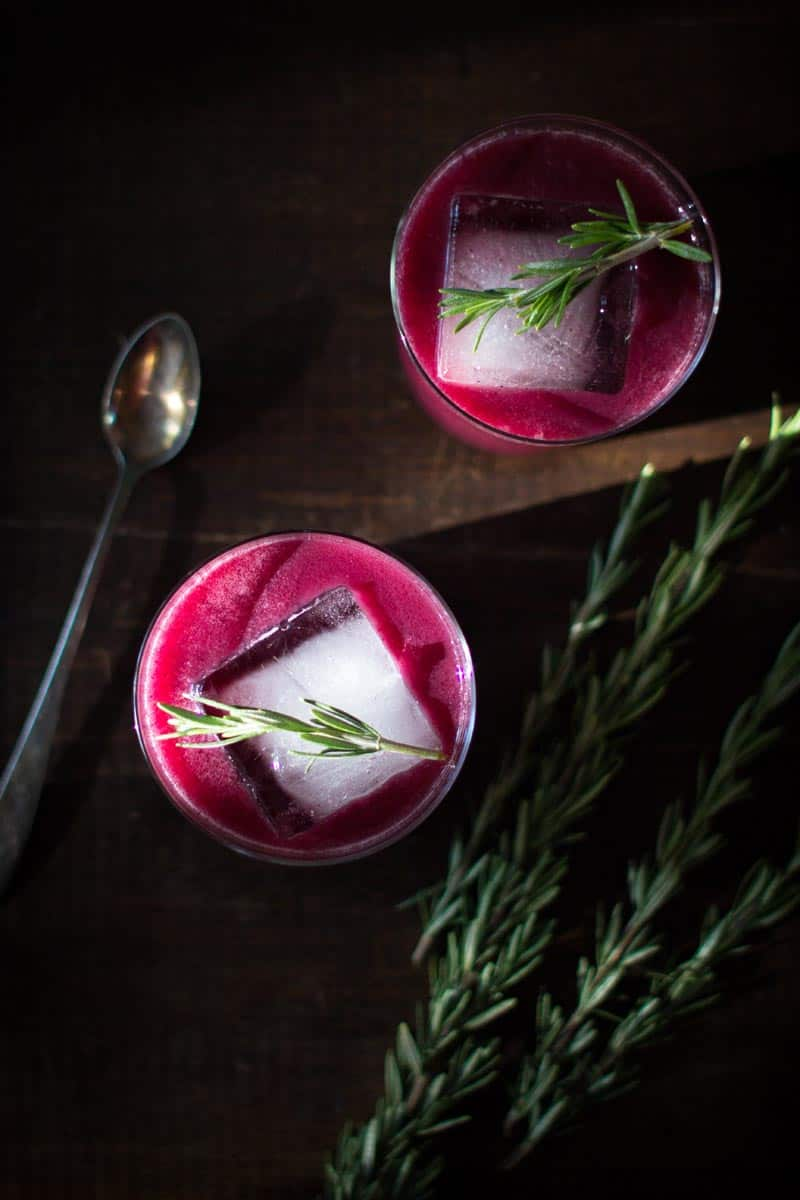 2 Stunning Rosemary Concord Grape Cocktails on a table