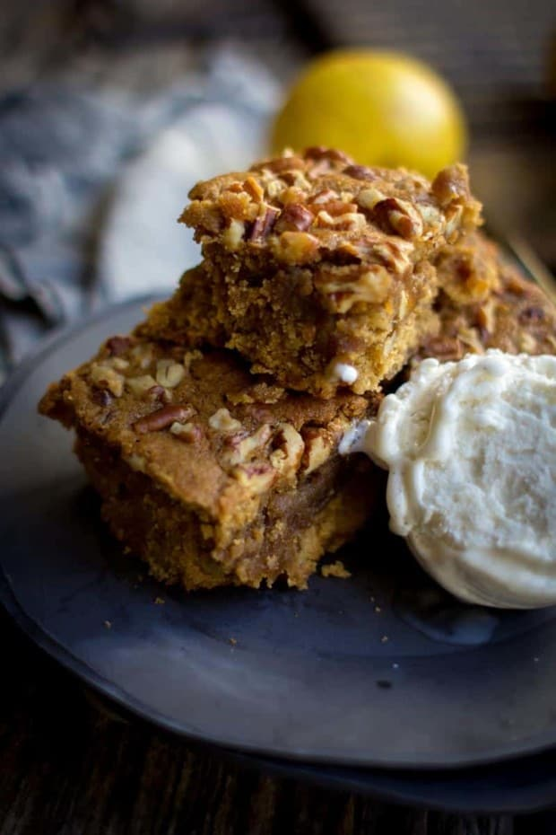 Three apple brown butter blondies are stacked on a black plate, 2 on the bottom and 1 on top, there is a scoop of vanilla ice cream next to the blondies