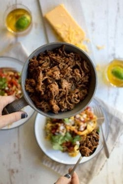 A skillet of Gluten Free Taco Spiced Ground Beef, a woman is spewing beef into assembled taco bowls