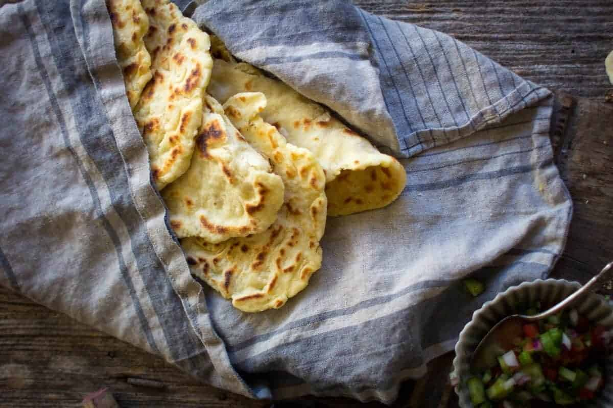 Gluten Free Roasted Garlic Naan in a basket lined with a linen cloth