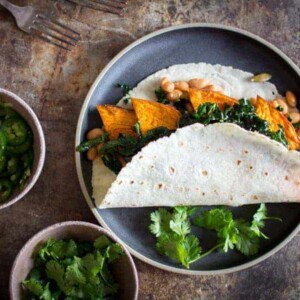 A taco filled with sweet potato, white beans, and greens