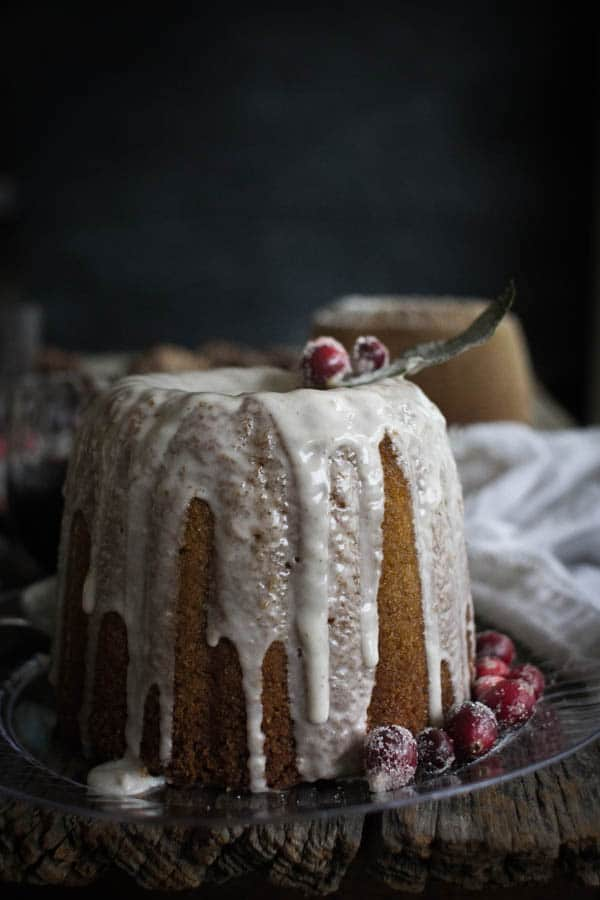 A bundt cake on a clear plate drizzled with eggnog icing and topped with sugared cranberries and bay leaves