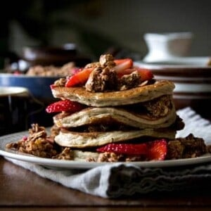 stack of pancakes with chocolate granola sprinkled over top and in batter, and strawberries