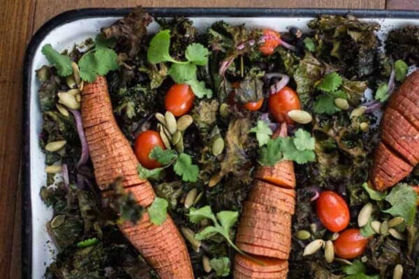 hasselback roasted sweet potatoes nestled in beds of crispy kale with black beans and tomatoes. Garnished with cilantro