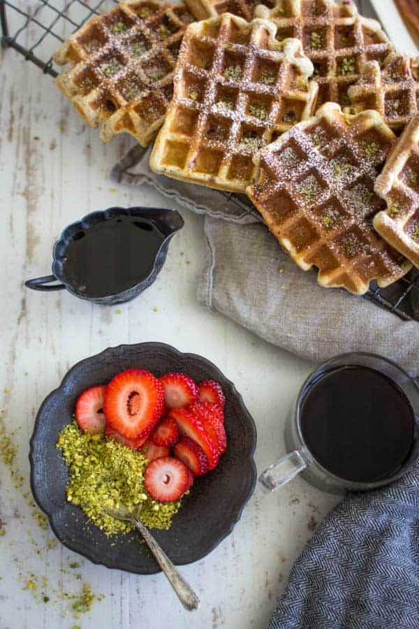 Decadent Strawberry and Pistachio Waffles dusted with powdered sugar. || @thismessisours