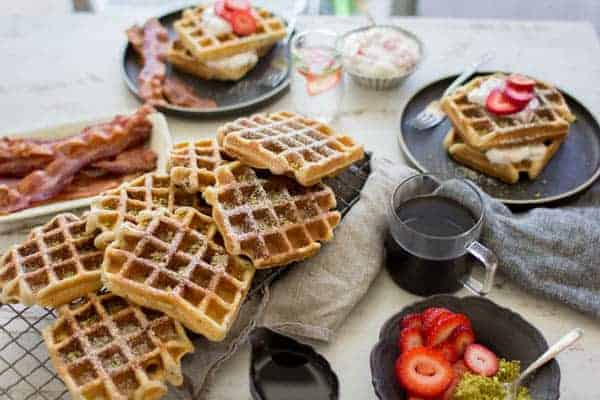 Decadent Strawberry and Pistachio Waffles dusted with powdered sugar and served with a side of crispy oven baked bacon.    @thismessisours