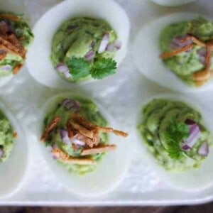 deviled eggs filled with guacamole filling and topped with crispy chips