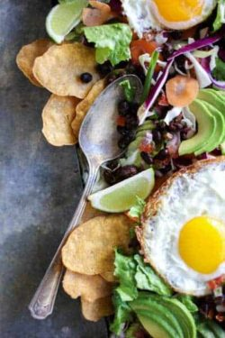fried eggs a top salad greens with black beans, salsa, and avocado