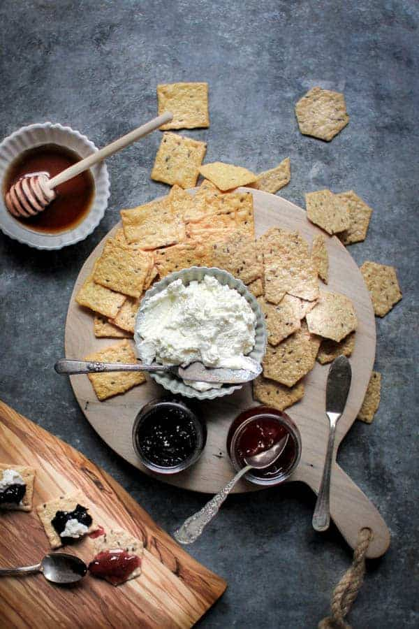 a wooden food board with homemade ricotta, strawberry jam, and blueberry jam and crackers.