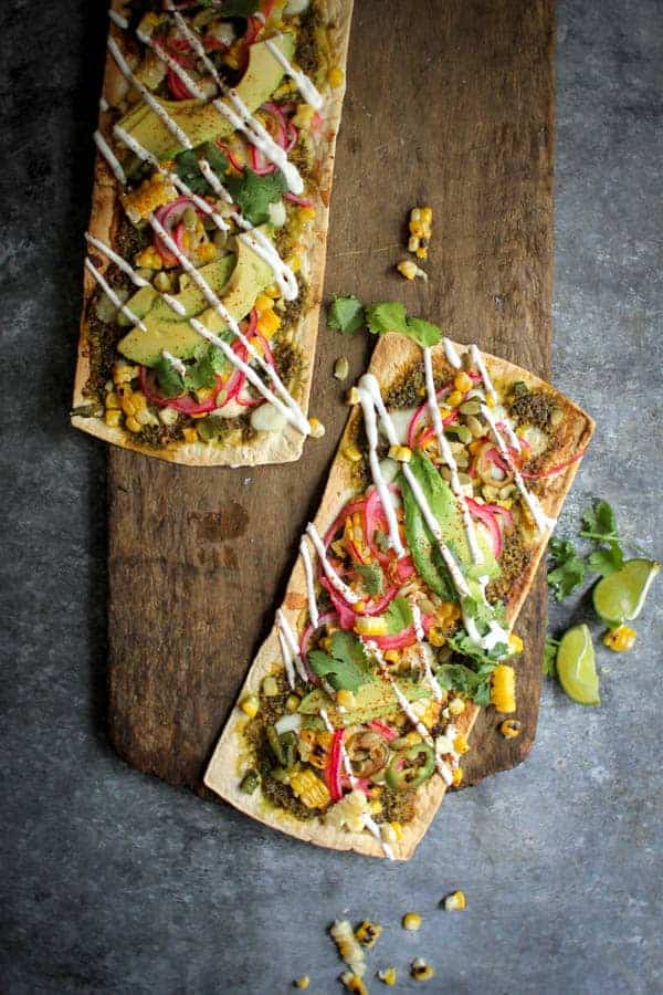 Grilled Mexican Street Corn Pizza recipe || Cilantro pistachio pesto + grilled corn + pickled red onions + avocado makes for one heck of a street corn inspired pizza! || @thismessisours @flatout #spon #flatoutlove