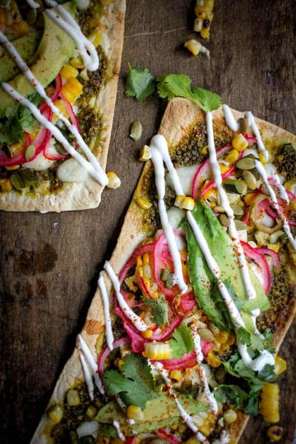 Grilled Mexican Street Corn Pizza recipe    Cilantro pistachio pesto + grilled corn + pickled red onions + avocado + cotija cheese makes for one heck of a street corn inspired pizza!    @thismessisours @flatout #spon #flatoutlove
