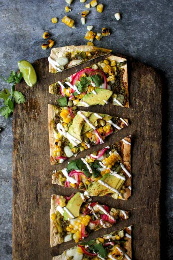 Grilled Mexican Street Corn Pizzas recipe || Cilantro pistachio pesto + grilled corn + pickled red onions + avocado makes for one heck of a street corn inspired pizza! || @thismessisours @flatout #spon