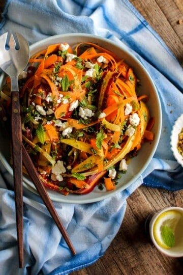 Carrot, Feta, and Pistachio Salad with Orange Blossom Toss dressing is on a table in a large serving bowl with utensils